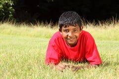 男孩草位于的公园红色少年佩带 免版税库存照片