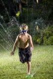 男孩草坪连续喷水隆头 库存图片