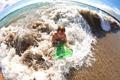 男孩获得与冲浪板的乐趣在波浪 免版税库存照片