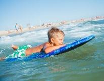 男孩获得与冲浪板的乐趣 免版税库存图片