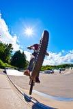 男孩获得与自行车的乐趣在冰鞋公园 免版税库存照片