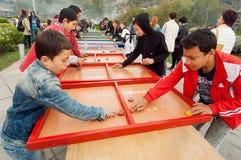 男孩获得乐趣在儿童操场的激情比赛期间 免版税库存图片