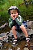 男孩获得乐趣在水中 免版税库存照片