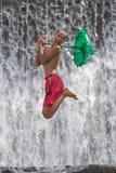 年轻男孩获得乐趣在瀑布 免版税库存照片