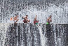 年轻男孩获得乐趣在瀑布 图库摄影