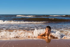 男孩获得在海滩的乐趣 免版税库存图片