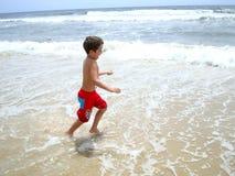 男孩获得在bigest和最美丽的海滩的乐趣英属黄金海岸澳大利亚 免版税库存图片