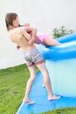 男孩获得帮助池的女孩 免版税库存图片