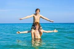 男孩获得背上使用的乐趣在温暖的海洋 库存图片