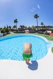 男孩获得跳的乐趣在室外水池 库存照片