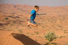 男孩获得飞跃与不尽的沙子的橙色沙丘的乐趣在背景和巨大的广播时间 库存照片