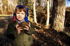 男孩藏品岩石 免版税图库摄影