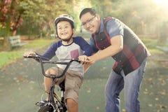 男孩行使骑有他的爸爸的一辆自行车 免版税库存照片