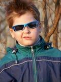 男孩表面玻璃做鬼脸他的 库存图片