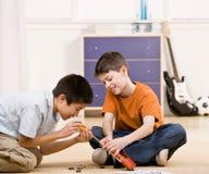 男孩被中断的解决朋友帮助的玩具 图库摄影