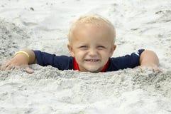 男孩被埋没的顶头对的少许沙子 库存图片