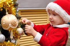 男孩装饰一棵新年度圣诞树 免版税库存照片