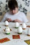 男孩装饰复活节的鸡蛋与贴纸 免版税图库摄影