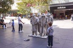 男孩观看的街道笑剧艺术家 免版税图库摄影