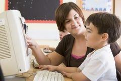 男孩计算机他的教师工作 库存图片