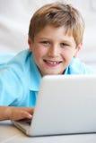 男孩计算机他的膝上型计算机年轻人 免版税库存照片