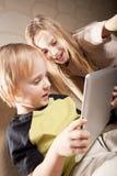 男孩计算机女孩微笑的片剂 库存照片