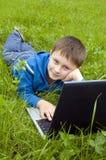 男孩计算机膝上型计算机草甸 库存图片