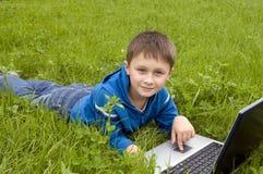 男孩计算机膝上型计算机草甸 图库摄影