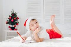 男孩认为他给圣诞老人会写信 免版税库存照片