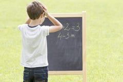 男孩认为,文字和计数在黑板 绿色室外背景 免版税库存图片