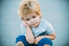男孩认为 蓝色路背景的体贴的学龄前儿童男孩 周详耽搁 孩子疲乏和 免版税库存图片