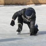 男孩设法在冰鞋的一个秋天以后起来 库存图片