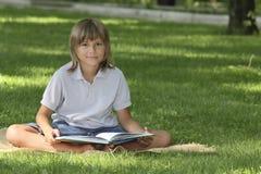 男孩读一本书 免版税库存图片