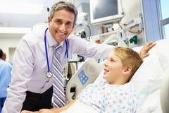 男孩谈话与男性顾问在急诊室 免版税图库摄影