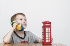 男孩谈话在电话和红色电话亭 库存照片