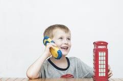 男孩谈话在电话和红色电话亭 库存图片