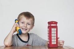 男孩谈话在电话和红色电话亭 免版税库存图片