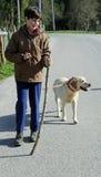 男孩走与他的在一条皮带的狗在途中 免版税图库摄影