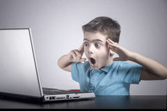 男孩起反应,当使用膝上型计算机时 库存照片
