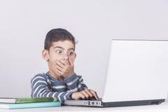 年轻男孩起反应,当使用膝上型计算机时 免版税库存照片