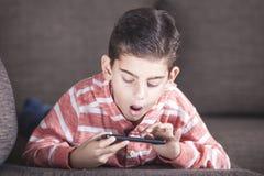 年轻男孩起反应,当使用他巧妙的电话时 免版税库存照片