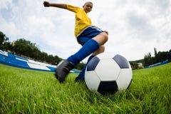 男孩足球运动员击中球 免版税库存图片