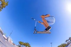男孩跳与他的滑行车在冰鞋公园 免版税库存照片