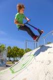 男孩跳与他的滑行车在冰鞋公园 免版税图库摄影