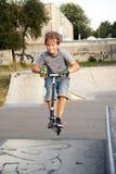 男孩跳与滑行车 图库摄影
