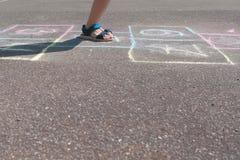 男孩跳演奏在街道的跳房子 特写镜头腿 侧视图 库存图片