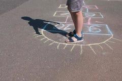 男孩跳演奏在街道的跳房子 特写镜头腿 免版税库存照片