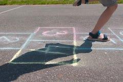 男孩跳演奏在街道的跳房子 特写镜头腿 免版税库存图片