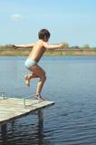 男孩跳的水 免版税库存照片