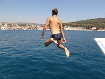 男孩跳的海运 库存照片